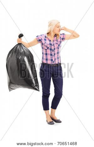 Full length portrait of a woman holding a smelly garbage bag isolated on white background