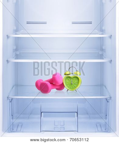Healthy lifestyle, diet concept. Green alarm clock heart shape and pink dumbbells  in empty refrigerator.