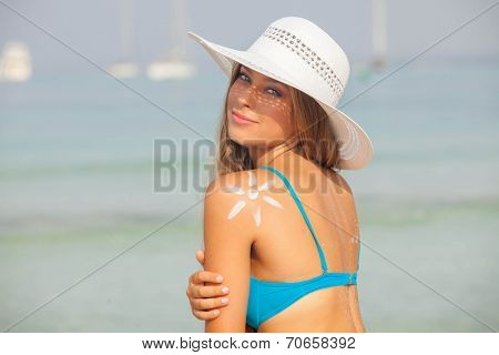 concept for safe sunbathing, woman with sun cream and hat