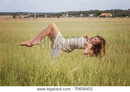 healthy woman floating in nature meadow, spa concept