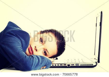 Beautiful bored and tired businesswoman lying down on desk next her laptop