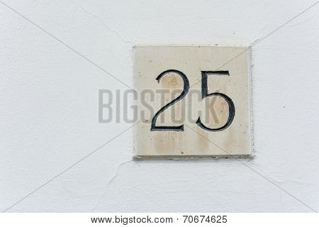 House Number Twenty Five On A Stone Plaque With A Green Wall Background