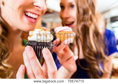 Friends having fun and eating muffins at bakery or pastry shop