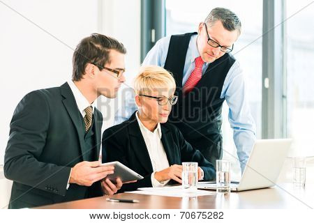 Business - meeting in office, businesspeople are discussing documents on Laptop and tablet computer