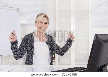 Cheering Senior Female Manager Sitting At Desk.