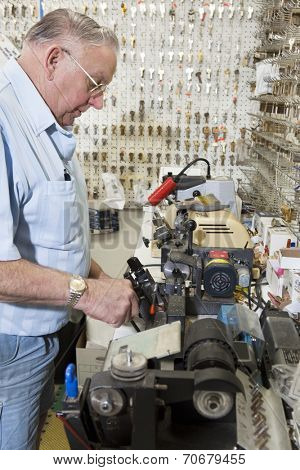 Side view of locksmith working in key store