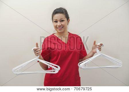 Portrait of female housekeeper holding white plastic hangers against gray background