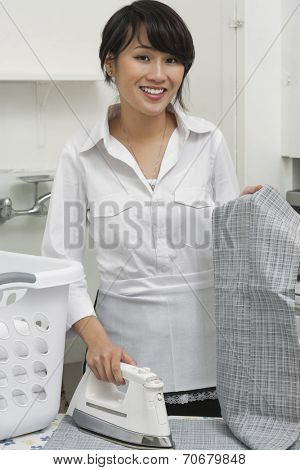 Portrait of young housemaid ironing trousers