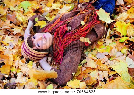 Portrait of a cute smiling woman looking at camera lying in autumn leaves in park, outdoor.