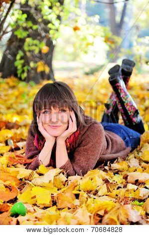 Smiling young woman portrait lying on her stomach in autumn park and looking at camera.