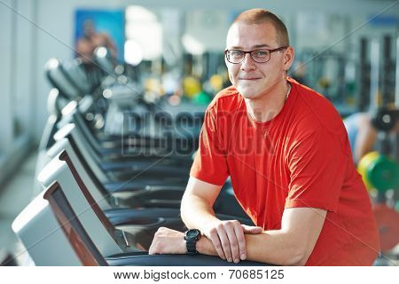 Smiling athlete bodybuilder man in front of barbell weights in fitness gym