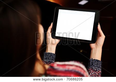 Back view portrait of a woman holding tablet computer
