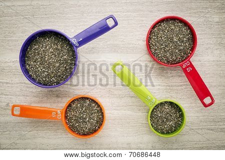 chia seeds in colorful, plastic, measuring cups against ceramic tile background - top view