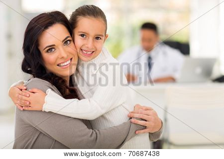 beautiful mother and daughter hugging in doctor's office