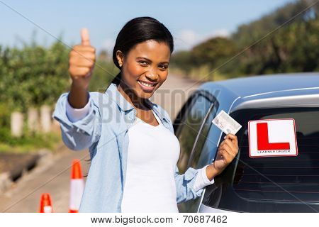 attractive african learner driver holding her driver's license