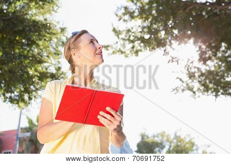 Blonde woman using her guide book on a sunny day