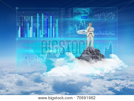 Thinking businessman against mountain peak through the clouds