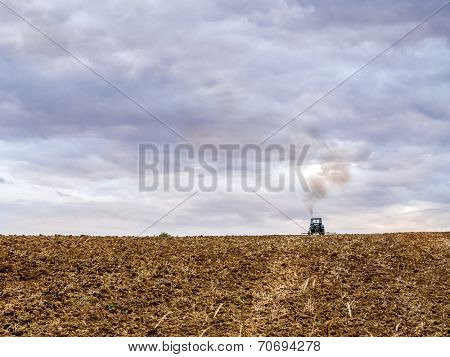 Farm tractor harrowing arable field