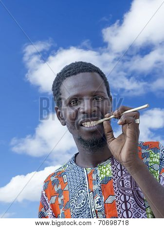 African man holding a miswak (traditional teeth cleaning twig)