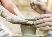 stock photo of pottery  - child learning how to make a pot on a pottery wheel - JPG