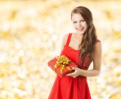 picture of congrats  - autumn present gift box smiling woman holding presents over fall leaves yellow background - JPG