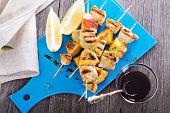 picture of baste  - Grilled pork kabobs with peaches served on a cutting board - JPG