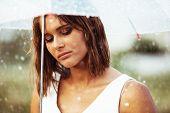 stock photo of bad mood  - Portrait of sad young girl walking with umbrella under rain - JPG