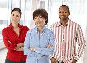 stock photo of arms race  - Team of happy caucasian business people standing in office looking at camera smiling - JPG
