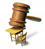 foto of court hammer  - Education law and school justice with a judge mallet or judges wooden gavel hammering a student class desk as a metaphor for public safety teacher or student abuse with a legal lawyer or attorney guidance for curriculum and learning issues - JPG