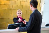 pic of check  - Man in Hotel check in at reception or front office being given key card - JPG