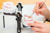 pic of dentures  - Female dental technician or orthodontist  producing denture with imprint - JPG