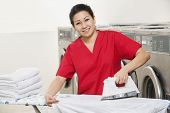 picture of laundromat  - Portrait of a happy woman employee in red uniform ironing clothes in Laundromat - JPG