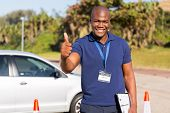 image of driving school  - portrait of handsome african driving school instructor giving thumb up - JPG