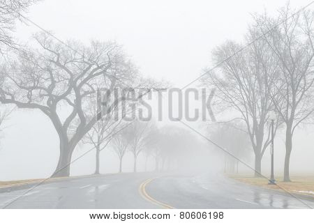 Asphalt road into fog