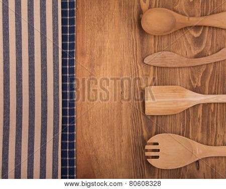 Blue and off white kitchen towels on dark wood background with a wooden utensils, with a slight vignette