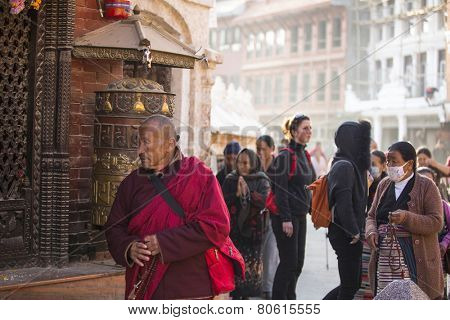 KATHMANDU, NEPAL - DEC 11, 2013: Unidentified Buddhist monk near stupa Boudhanath. Stupa is one of the largest in the world, of 1979 is a UNESCO World Heritage Site.