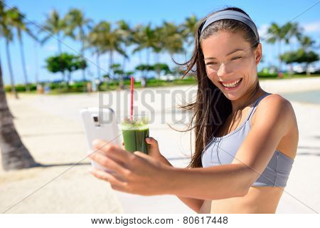 Fitness selfie woman drinking green vegetable smoothie taking self portrait photograph with smart phone after running exercise workout on beach. Healthy lifestyle with fit Asian Caucasian girl.
