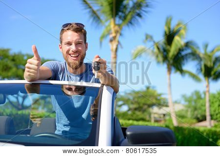 Car driver showing keys and thumbs up happy. Young man holding car key for new leasing convertible. Rental cars or drivers licence concept with male driving cabriolet on road trip.