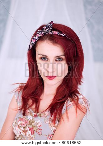 Pretty redhead woman in a floral summer dress with matching headband looking at the camera with a sultry serious expression