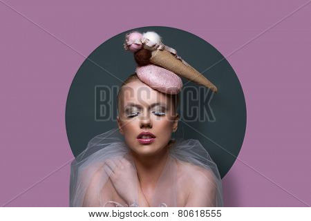 Fine art portrait of a gorgeous woman in fascinator hat in the shape of an ice cream cone with creative makeup and filmy gauze around her shoulders over a purple background