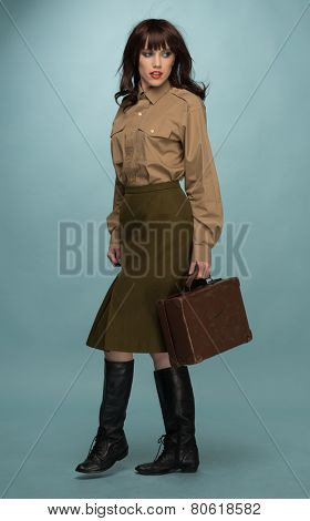 Full Length of Fashionable Young Woman In Trendy Clothing and Black Boots Carrying Suit Case on Light Blue Green Background.