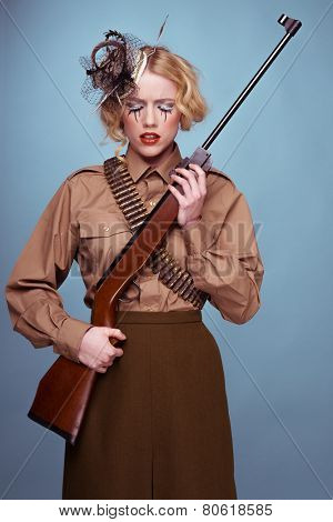 Glamour portrait of a pretty blond woman wearing an elegant fascinator hat in army uniform with ammunition and a rifle over blue