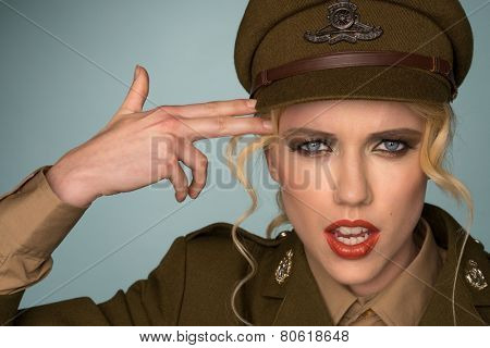 Pretty young blond woman in a peaked cape and army uniform making a gun gesture pointing her two fingers at her temple while looking intently at the camera with parted lips
