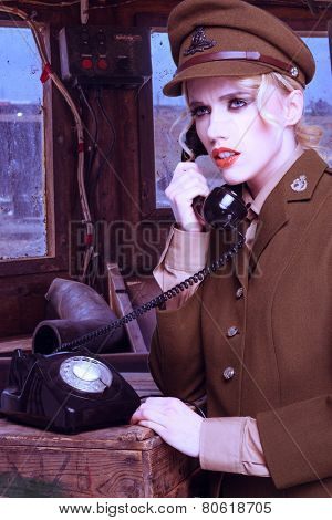Pretty blond woman in a brown army uniform standing talking on a retro dial-up telephone on a wooden crate in a barracks