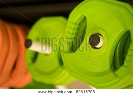 Colorful weights of different sizes for dumbbells and weightlifting equipment in the gym, closeup focus onto a single green weight