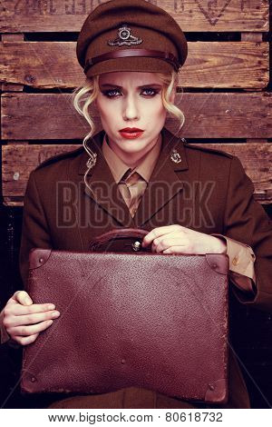 Glamorous intense young female army recruit with blond ringlets clutching an old leather suitcase sitting gazing at the camera against a wooden wall