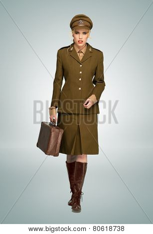 Glamorous woman in a stylish brown military uniform walking towards the camera carring an attache case, over grey