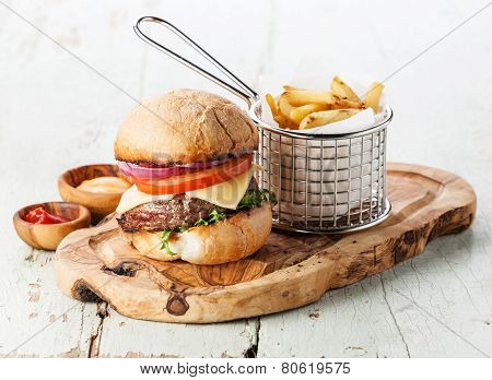 Burger With Meat And French Fries In Basket On Wooden Background