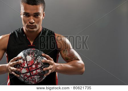 Young handsome African man playing basketball