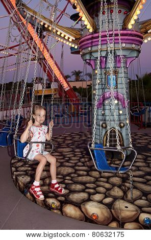 Child rides a carousel in the evening park.
